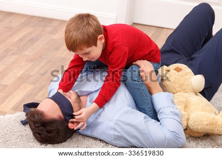 Cheerful young father and his son are making fun. The man is lying on the floor and carrying his kid. The boy is sitting and covering male eyes with the tie. They are smiling happily - stock photo