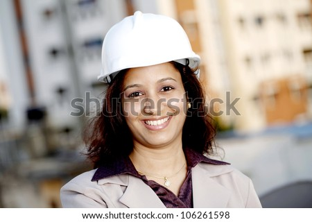 Cheerful young female architect at construction site - stock photo