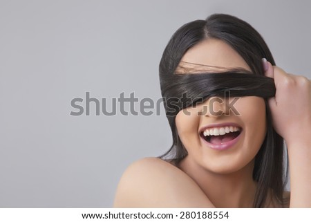 Cheerful young female covering eyes with her hair over colored background - stock photo