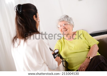 cheerful young female doctor taking blood pressure of an elderly woman at home