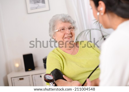 cheerful young female doctor taking blood pressure of an elderly woman at home - stock photo