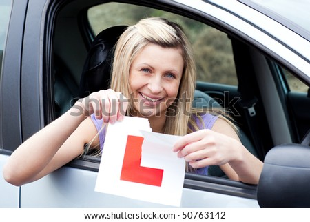 Cheerful young female driver tearing up her L sign sitting in her car - stock photo