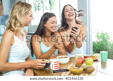 Cheerful young female friends having breakfast while using mobile phone at home - stock photo