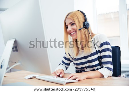 Cheerful young female operator with headset using desktop computer in office - stock photo