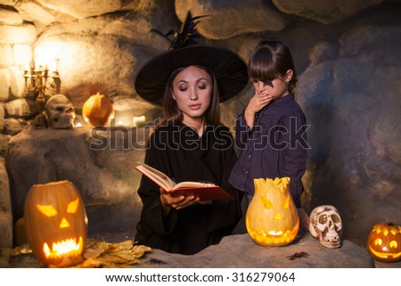 Cheerful young female wizard is teaching her daughter to conjure in Halloween. She is holding an open book of spells with aspiration. The girl is looking at it with shock and fear - stock photo