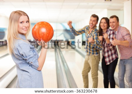 Cheerful young friendly team in kegling club - stock photo
