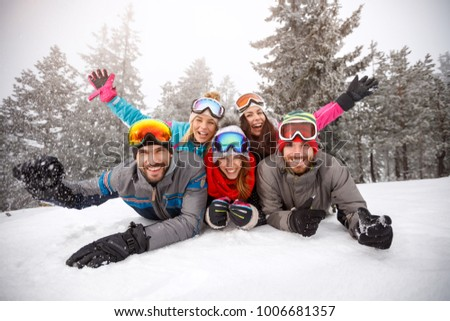 Cheerful young friends on skiing laying together on snow