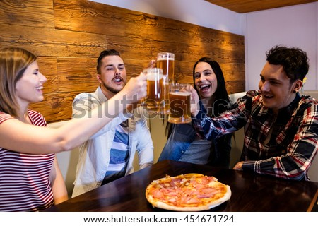 Cheerful young friends toasting beer at bar