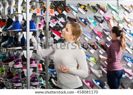 Cheerful young girl choosing shoes in the sport store - stock photo