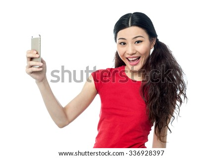 Cheerful young girl clicking a picture