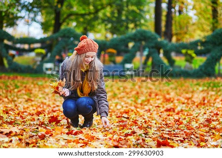 Cheerful young girl gathering autumn leaves in park
