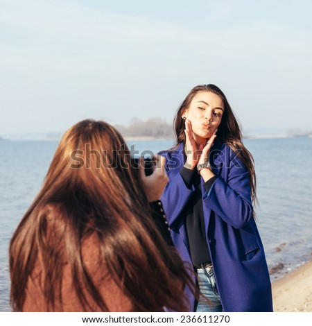Cheerful young girl in a blue coat posing her girlfriend on the beach in front of the sea Outdoor lifestyle portrait - stock photo