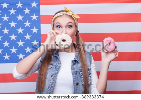 Cheerful young girl is eating American food - stock photo