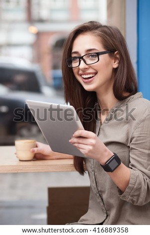 Cheerful young girl is using modern gadget