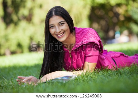 Cheerful young girl lying on grass in park, reading magazine