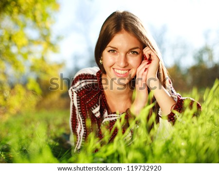 Cheerful young girl lying on green grass close up,in summer park. - stock photo