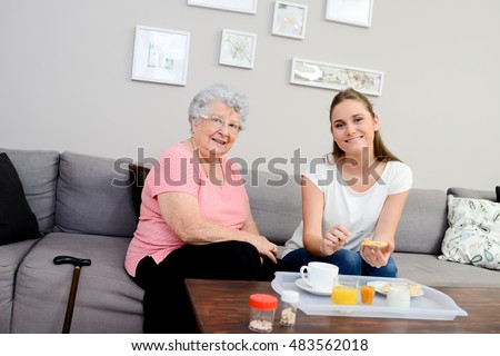 cheerful young girl serving breakfast to an elderly woman at home