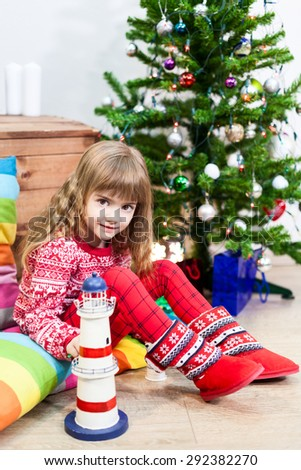 Cheerful young girl weared red fur boots sitting near the Christmas tree - stock photo