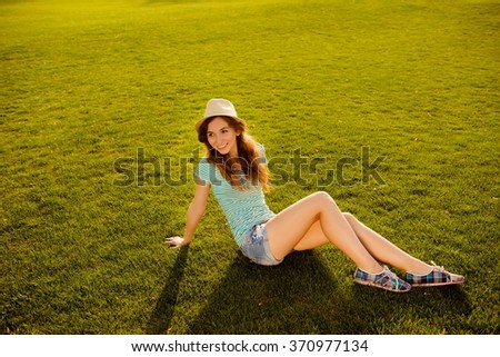 Cheerful young girl with hat sitting on the grass