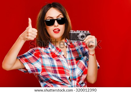 Cheerful young girl, with short dark hair, wearing in checkered shirt and sunglasses, posing with retro camera on red background, in studio, waist up - stock photo