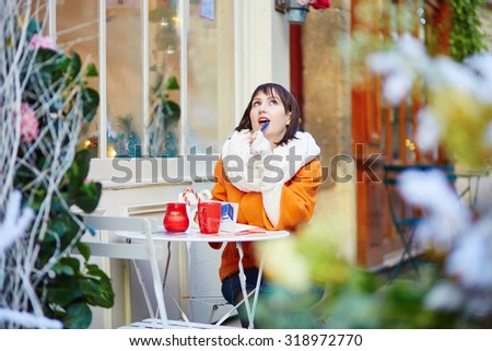 Cheerful young girl writing Christmas cards or New Year resolutions in Parisian outdoor cafe - stock photo
