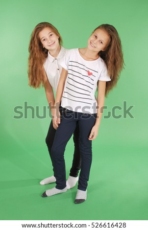 Cheerful young girls are standing against the green background