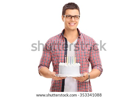 Cheerful young guy holding a birthday cake and looking at the camera isolated on white background