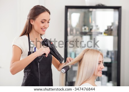 Cheerful young hairdresser is drying human hair with hair-drier. She is standing and smiling. The blond woman is sitting and looking forward with joy