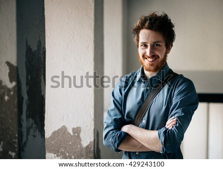 Cheerful young hipster guy posing and smiling at camera with crossed arms - stock photo