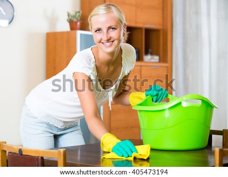 Cheerful young housewife in rubber gloves dusting furniture at home - stock photo