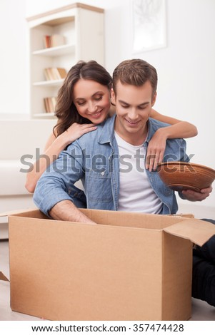 Cheerful young husband and wife are moving in new house. They are packing things into cardboard boxes and smiling. The woman is embracing the man with love - stock photo