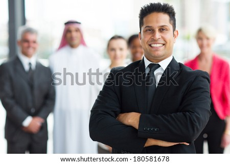 cheerful young indian businessman with team on background - stock photo