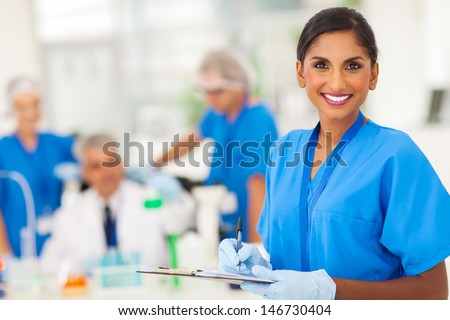 cheerful young indian medical researcher writing report in the lab - stock photo