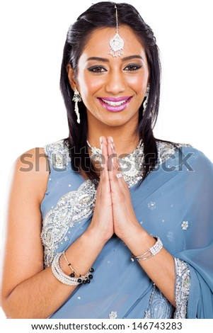 cheerful young indian woman praying isolated on plain background