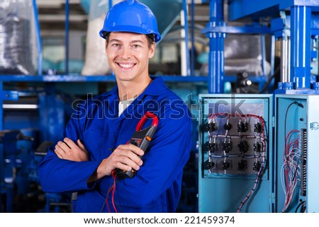 cheerful young industrial technician looking at the camera - stock photo