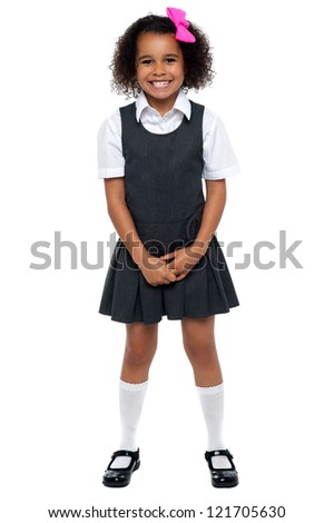 Cheerful young kid in pinafore dress posing smilingly isolated on white background. - stock photo