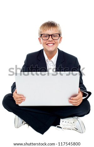 Cheerful young kid sitting on the floor with a laptop. Isolated over white background - stock photo