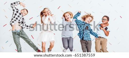 Cheerful young kids jumping in the air with a smile on their faces