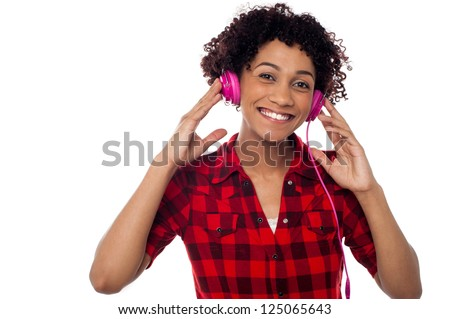 Cheerful young lady listening to lively music via pink headphones.
