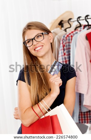 Cheerful young lady with shopping bags and plastic card buying clothes in retail store. Happy female customer posing at the rack with clothing.  - stock photo