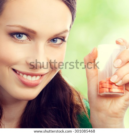 Cheerful young lovely brunette woman showing bottle with pills, outdoor - stock photo