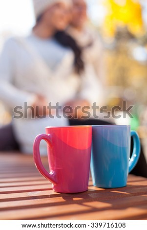 Cheerful young loving couple is dating in the autumn park. They are sitting on bench and embracing. The man and woman are smiling. Focus on two cups of hot coffee - stock photo