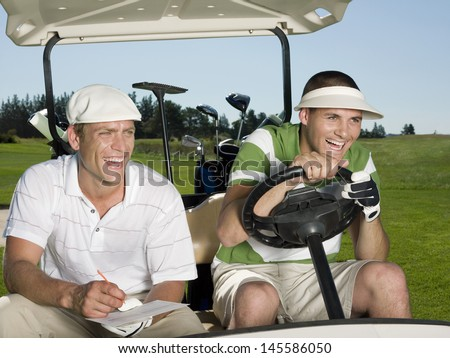 Cheerful young male golfers sitting in golf cart at course - stock photo