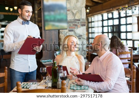 Cheerful young male waiter serving restaurant guests at table. Selective focus - stock photo
