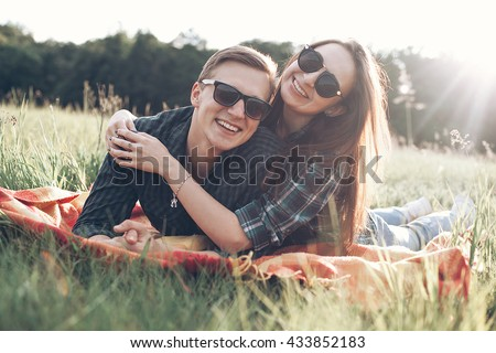 Cheerful young man and girl lie outdoors in the sunlight