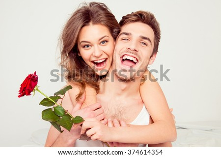 Cheerful young man and woman in love hugging in the bedroom with rose - stock photo