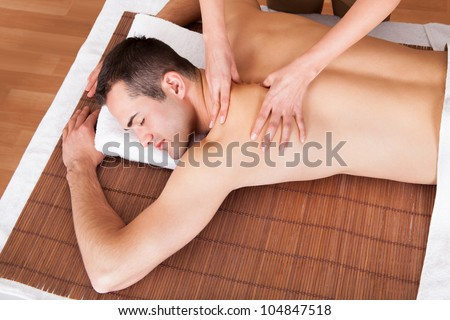Cheerful young man getting shoulder massage at spa - stock photo