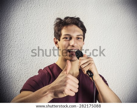 Cheerful young man holding a microphone - stock photo