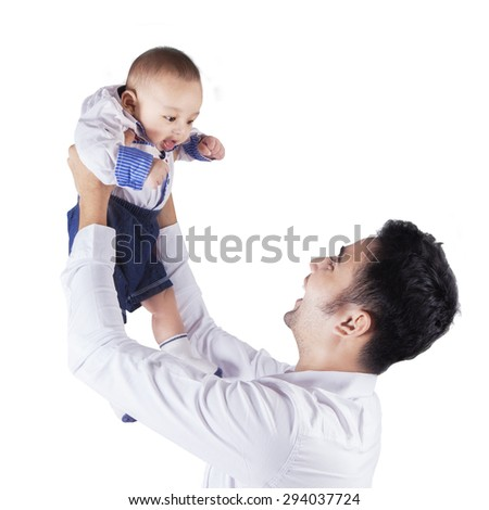 Cheerful young man holding and playing with a smiling 0-4 months old baby - stock photo
