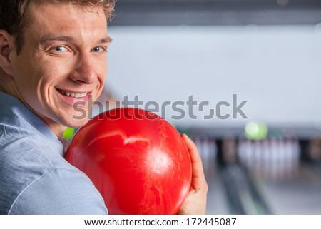 Cheerful young man holding bowling ball. Cheerful young man at the bowling alley, he is holding a bowling ball and looking at camera.